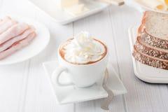 Una tazza di caffè con la crema del wheap Fotografie Stock