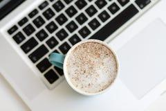 Una tazza di caffè con la gomma piuma del latte su un computer portatile Fotografia Stock