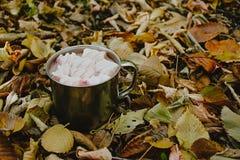 Una tazza di caffè con le caramelle gommosa e molle su un fondo delle foglie gialle fotografia stock