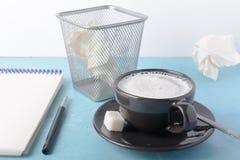 Una tazza di caffè con schiuma lattea, un taccuino aperto Urna con carta sgualcita Priorità bassa per una scheda dell'invito o un immagine stock