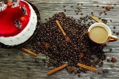 Una tazza di caffè con un grande dolce ed i chicchi di caffè, l'anice e la cannella su una tavola di legno immagine stock libera da diritti