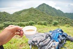 Una tazza di caffè disponibila con backpage e la montagna è fondo Immagini Stock