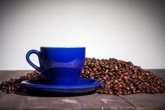 Una tazza di caffè e chicchi di caffè sulla tavola di legno Immagine Stock