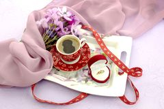 Una tazza di caffè e un anello di diamante Fotografia Stock