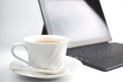 Una tazza di caffè e un computer portatile su fondo bianco immagine stock