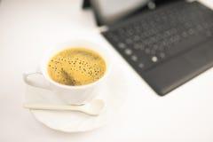 Una tazza di caffè e un computer portatile su fondo bianco immagini stock libere da diritti