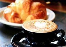 Una tazza di caffè e un croissant Fotografia Stock