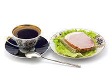 Una tazza di caffè e una zolla con un panino. Fotografia Stock Libera da Diritti