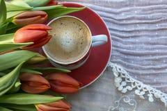Una tazza di caffè espresso con i tulipani rossi immagini stock