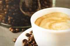 Una tazza di caffè espresso cremoso davanti al contenitore di chicco di caffè Fotografia Stock Libera da Diritti