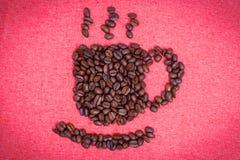 Una tazza di caffè fa dai chicchi di caffè sul fondo rosso del panno Fotografia Stock