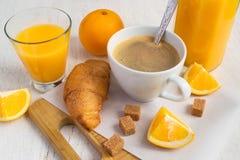 Una tazza di caffè, le arance fresche, un succo d'arancia e un croissant Fotografie Stock