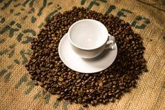 Una tazza di caffè macchiato circondata dai chicchi di caffè Fotografia Stock