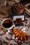 Una tazza di caffè nero con una ciambellina salata, un mulino di caffè ed i chicchi di caffè sparsi su una tavola coperta di tela fotografia stock