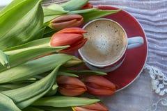 Una tazza di caffè nero con i tulipani rossi fotografia stock