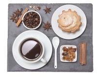 Una tazza di caffè nero con il bigné, sul piatto di pietra nero, vista superiore Pausa caffè della prima colazione di mattina sul Fotografia Stock Libera da Diritti
