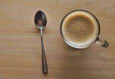 Una tazza di caffè nero e caldo sulla vecchia tavola di legno Fotografia Stock