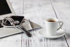 Una tazza di caffè nero e delle attrezzature casuali di affari sul bordo di legno fotografie stock