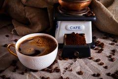 Una tazza di caffè nero, di un mulino di caffè e dei chicchi di caffè sparsi su una tavola coperta di tela da imballaggio fotografia stock