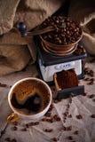 Una tazza di caffè nero, di un mulino di caffè e dei chicchi di caffè sparsi su una tavola coperta di tela da imballaggio immagine stock