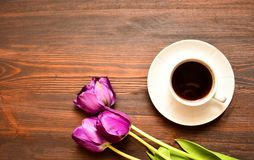 Una tazza di caffè o un tè su un piattino sta su un fondo di legno, tulipani porpora si troverà dopo immagine stock libera da diritti