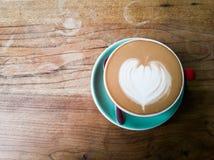 Una tazza di caffè rossa con il modello del cuore su fondo di legno Immagine Stock Libera da Diritti