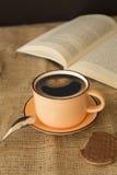 Una tazza di caffè sorridente con un libro Fotografia Stock
