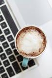 Una tazza di caffè su un computer portatile Immagini Stock