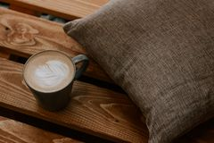 Una tazza di caffè su un fondo di legno con un cuscino grigio, tempo del caffè fotografie stock libere da diritti