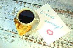 Una tazza di caffè su un piattino, su un pancake di recente al forno e su pezzo di carta con un desiderio del buongiorno e una tr immagini stock libere da diritti