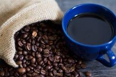 Una tazza di caffè sui chicchi di caffè immagini stock libere da diritti