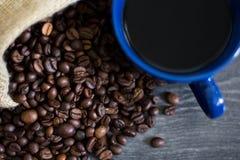 Una tazza di caffè sui chicchi di caffè fotografia stock