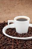 Una tazza di caffè sui precedenti dei chicchi di caffè Fotografie Stock Libere da Diritti