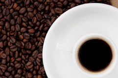 Una tazza di caffè sui precedenti dei chicchi di caffè Immagine Stock Libera da Diritti