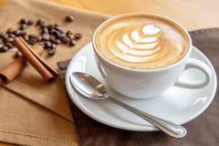 Una tazza di caffè sul tovagliolo marrone Fotografia Stock