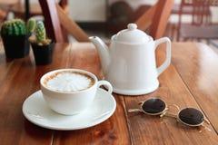 Una tazza di caffè sulla tavola in caffè con i vetri immagine stock