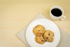 Una tazza di caffè, tre pezzi di biscotti di pepita di cioccolato in un piatto rotondo bianco fotografie stock libere da diritti