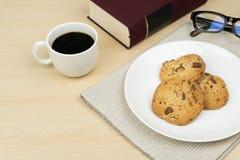 Una tazza di caffè, tre pezzi di biscotti di pepita di cioccolato in un piatto rotondo bianco, un libro rosso ed occhiali Fotografia Stock Libera da Diritti