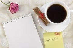 Una tazza di caffè, un taccuino, un autoadesivo del vostro caffè, una rosa, su una decorazione bianca del fondo immagini stock libere da diritti
