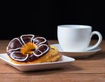 Una tazza di caffè con la ciambella del cioccolato zuccherato Immagine Stock