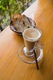 Una tazza di cappuccino e di pane caldi Immagine Stock