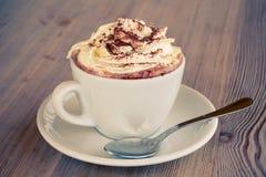 Una tazza di cioccolato caldo con crema su una tabella Fotografia Stock