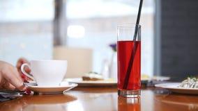 Una tazza di coffe e un vetro della bevanda sulla tavola Una mano della donna prende lo zucchero e lo ha messo nella tazza, un'al video d archivio
