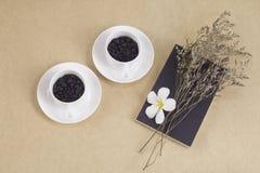 Una tazza di due bianchi con i chicchi di caffè su carta marrone Immagini Stock