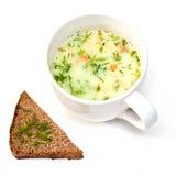 Una tazza di minestra istante e una fetta di pane Fotografie Stock