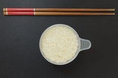 Una tazza di riso con un paio dei bastoncini Fotografia Stock