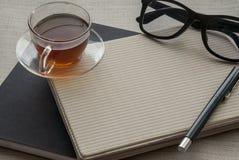 Una tazza di tè è sul taccuino per lavoro immagine stock