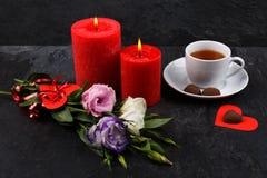 Una tazza di tè accanto ad una caramella su un cuore, un mazzo delle rose e rose brucianti su un fondo di pietra Fotografia Stock
