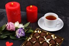 Una tazza di tè accanto ad una scatola di cioccolato e ad un mazzo delle rose su un fondo di pietra Fotografia Stock