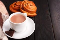 Una tazza di tè al latte, parecchie fette di cioccolato e due panini con le ciliege fotografia stock libera da diritti